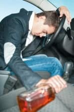 Young driver with bottle in hand sleeps in the car.